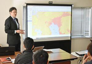 ハザードマップを示しながらBCPの必要性を呼び掛けた亀﨑洋氏(左)=佐賀市の日産サティオ佐賀P〓s佐賀店