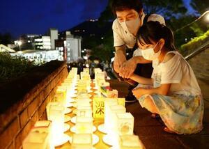 被爆から75年の原爆の日を前に、平和への願いを込め並べられたキャンドルを見つめる親子=8日夕、長崎市の平和公園