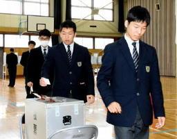 伊万里市選管から借りた実際の投票箱に票を投じる生徒=伊万里市の敬徳高校