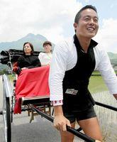由布岳を背に人力車を引く津田貴之さん。力強い足取りで地震からの復興を目指す