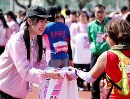 ファンランの完走者にタオルを手渡すボランティア=県総合運動場補助競技場