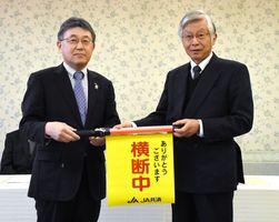 横断旗を贈呈するJA共済連佐賀の大串成幸本部長(左)と県交通安全協会の坂井邦夫会長=佐賀市のホテルグランデはがくれ