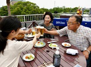 佐賀城のお堀を見下ろす屋上で友人とビールを楽しむ夫婦。感染対策で卓上には消毒液(手前)も置かれている=佐賀市のホテルニューオータニ佐賀(撮影・山口源貴)