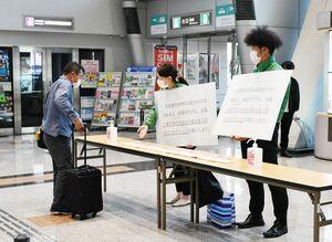 パネルを見せながら外出自粛を呼び掛ける県職員=佐賀市川副町の佐賀空港
