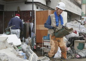 民家に流れ込んだ泥を運び出すボランティアの男性=10日午前、福岡県朝倉市