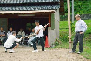 大人やお年寄りから伝統芸能「災払」の演目の手ほどきを受ける子どもたち=基山町の仁蓮寺地区