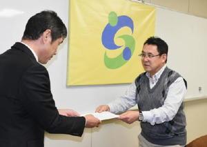 佐賀市の担当職員にアンケート結果を提出する松永会長=佐賀市役所