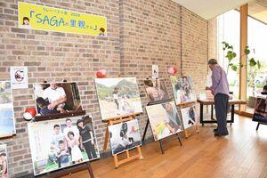 里親との家庭での様子を写した18点の写真が並ぶリレーパネル展「SAGAの里親さん」=武雄市図書館