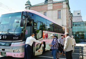 旧唐津銀行の見学を終え、バスに乗り込む前に手指消毒をするツアー参加者たち