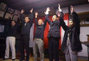 初当選を果たし、母ユキ子さん(右)と万歳三唱をする久米勝也さん(右から2人目)=15日午後11時15分ごろ