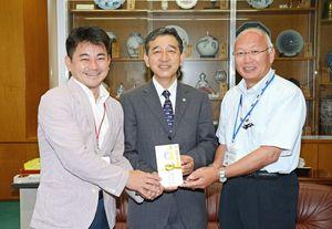 曲川小の坂井禎校長(右)に寄付の目録を手渡した、ありたの池田憲正社長(中央)。左は松尾佳昭町長=有田町役場
