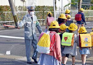 児童とあいさつを交わしながら交通指導員をする山下剛司さん=伊万里市大坪町