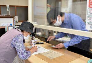 新型コロナワクチン接種の予約を手伝う伊万里市職員(右)=同市黒川町のコミュニティセンター