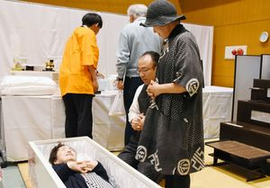 入棺を体験する参加者=佐賀市のメートプラザ佐賀