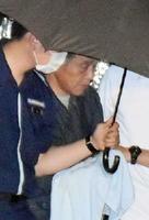 東京から移送され、唐津海上保安部の庁舎に入る山崎竹助容疑者(中央)=6日午後7時52分