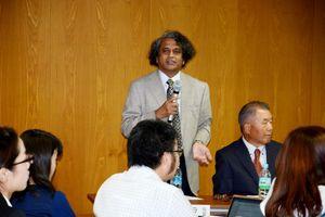 外国人技能実習制度に関する調査結果を説明するラタナーヤカ名誉教授。右側はイイダ靴下の飯田会長=佐賀市の佐賀大学