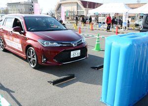 衝突を軽減するシステムを搭載した自動車に乗って機能を体験する参加者=佐賀市のメートプラザ佐賀駐車場