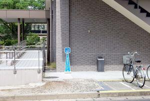 駐輪場や建物の出入り口に通じるスロープに隣接している喫煙所=佐賀大学理工学部大学院棟(提供写真)