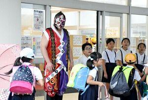 登校する児童をあいさつで迎える覆面レスラーの将火怒さん=佐賀市の金立小