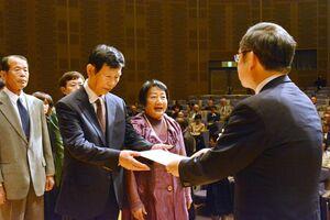 佐賀新聞社の中尾清一郎社長(右)から表彰状を受ける金婚さん夫妻=佐賀市のアバンセ