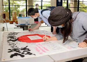 車いすテニスの大谷桃子選手への応援メッセージを書く人たち=佐賀市の佐賀県庁県民ホール