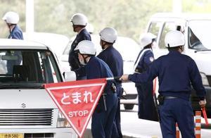 広島県尾道市・向島を出る車両を検問する警察官=17日午後