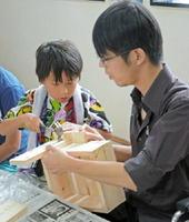 親子で協力して椅子を作り上げる作業風景=佐賀市北川副町の櫻工夢店