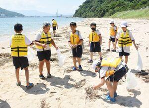 地引き網体験後、砂浜のごみを拾う児童たち=唐津市の幸多里の浜
