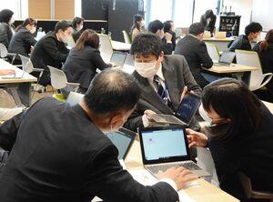学習用タブレット端末を操作し、活用法を学ぶ中学校教諭ら=神埼市役所