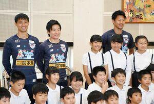 東脊振小の児童とクラスごとに記念撮影するサガン鳥栖の選手たち=吉野ヶ里町の同校