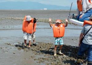 漁船から自然のカキ礁の上に降り、観察する子どもたち=嘉瀬川河口