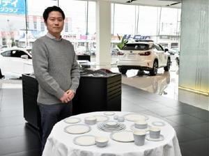 トヨタの高級ブランド車が並ぶ店内で、個性的な作品を出展している照井壮さん=佐賀市鍋島町のレクサス佐賀
