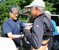 登山参加者に心拍計を着ける山本正嘉教授(左)=5月、佐賀市の金立山