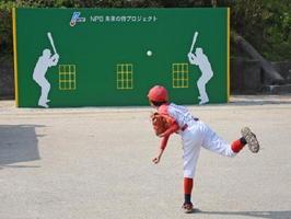 日本野球機構から贈られたベース・ウォールで始球式をする児童=伊万里市の山代東小学校