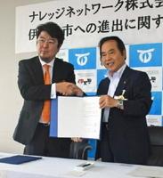 進出協定を交わしたナレッジネットワークの森戸裕一社長(左)と塚部芳和市長