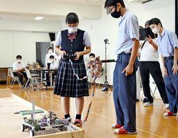 ゴルフボールを取ろうと、懸命にリモコンを操作する生徒たち=佐賀市の佐賀工高