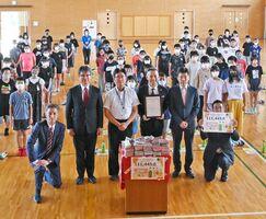 贈呈式に参加したキリンビバレッジやダイレックスの関係者や児童たち=佐賀市の高木瀬小