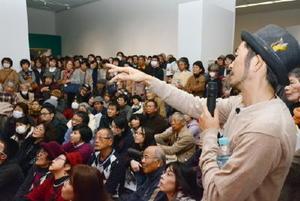 詰め掛けた来場客に自作を解説する池田学さん(右)=佐賀市の県立美術館