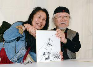 松本零士さんと人気キャラクターを描いたサイン色紙とともに記念撮影するファン=有田町の町役場東出張所広場