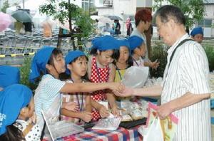 手作りのパンや菓子を販売し、客とのやりとりを楽しむ小学生たち=佐賀市の白山アーケード