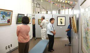 油彩や水彩画などが並んでいる作品展=吉野ヶ里町のJR吉野ヶ里公園駅コミュニティーホール