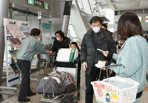 日本への肉製品の持ち込みを禁止する啓発用ティッシュを配り、注意喚起する職員たち=佐賀市の佐賀空港