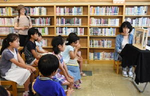 読み聞かせを行うほんだひろこさん(右)と妹の森川聖子さん(左)=佐賀市城内の県立図書館