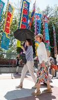 大相撲夏場所が開かれている東京・両国国技館ののぼりの前を日傘を差して歩く女性=25日午前