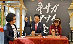 浮立面を設置したお盆で出される「浮立麺-激辛つけ面-」を味わう山口祥義知事(中央)ら=佐賀県庁新館地下1階のSAGA CHIKA