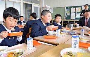 ご飯も提供された給食を笑顔で食べる児童と笑顔で見守る伊東町長=吉野ヶ里町の三田川小学校