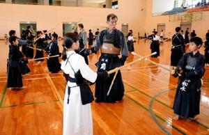 範士八段を持つ角さんに教わりながら、竹刀の振り方を学ぶ子どもたち=東松浦郡玄海町の町民会館