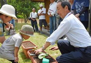 苗植えの実演をする葉隠緑化建設の相良善次さんと苗植えを手伝った子ども=佐賀市の佐賀県立森林公園