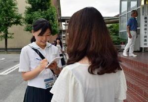 初めて投票した感想などを若い有権者に質問した弘学館高校の新聞部員(左)=佐賀市の鍋島中の投票所