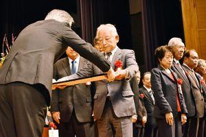 表彰状を受け取る保護司=佐賀市の東与賀文化ホールふれあい館